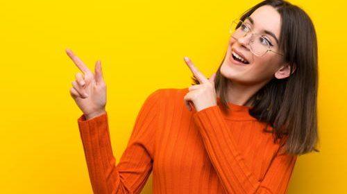 Ein Mädchen vor einem gelben Hintergrund freut sich über die Leistungen von Stellenanzeigenwerk.